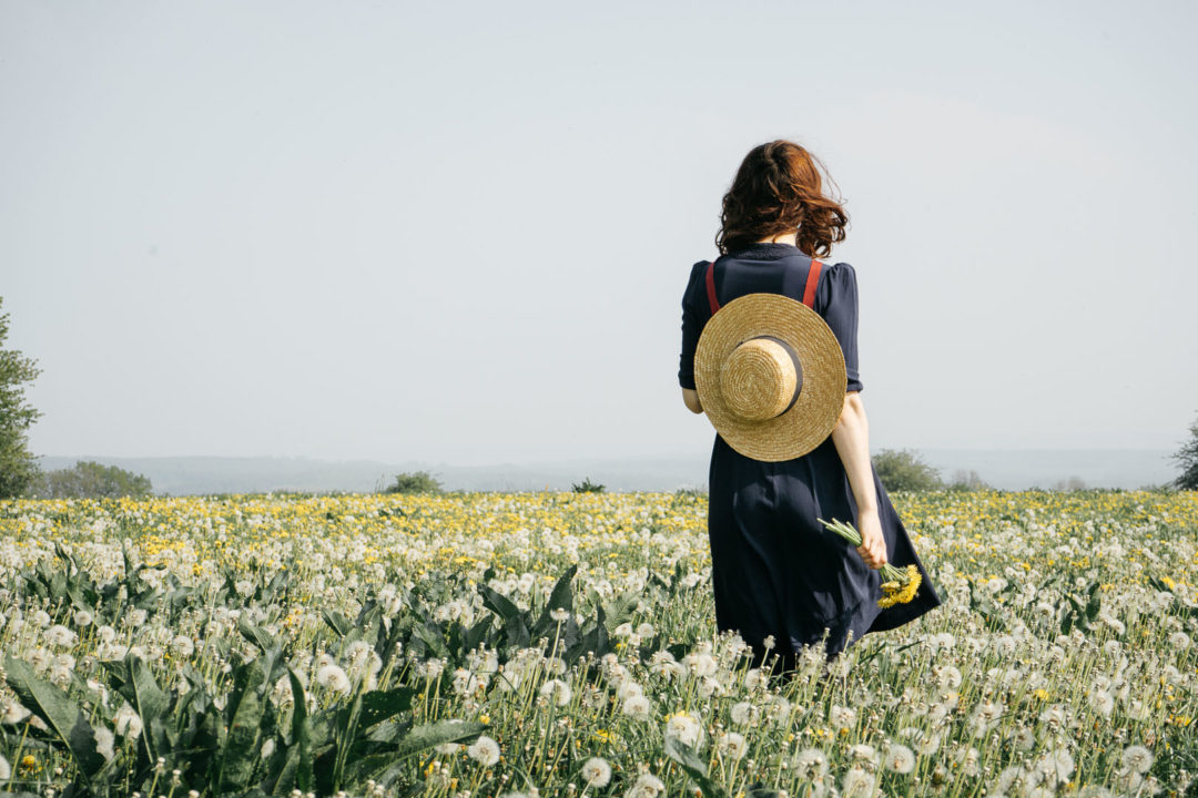 Girl with a hat in a dandelion meadow during May
