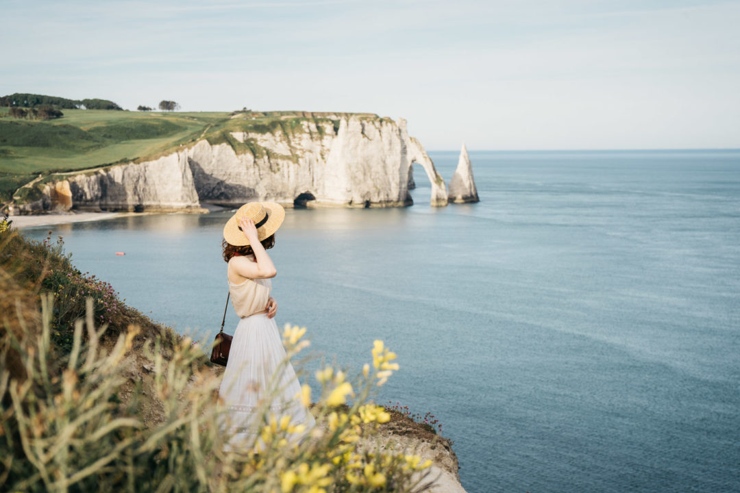 Girl standing in front of the cliffs in Étretat