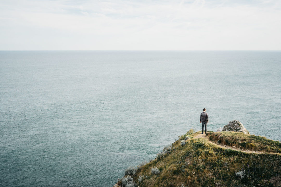 Man overlooking the vast sea in Étretat