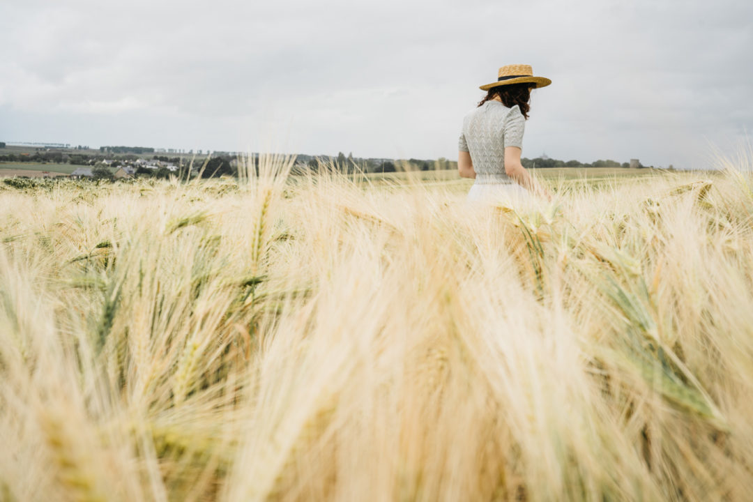 Girl walking through a field of barley in June