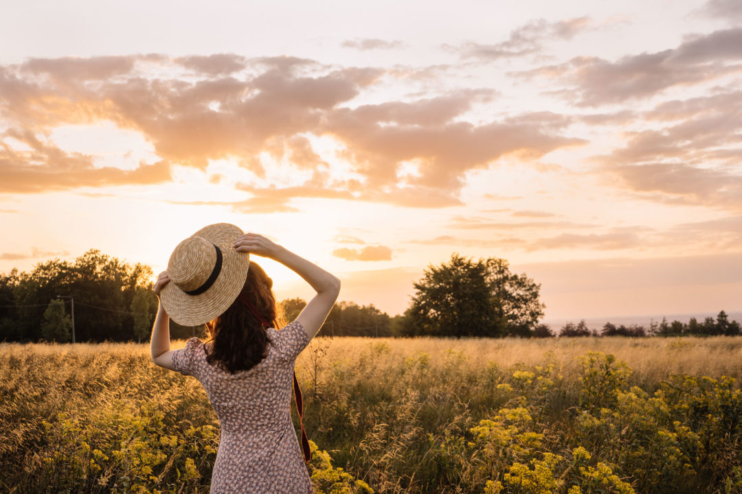 Girl holding a hat during an August sunset