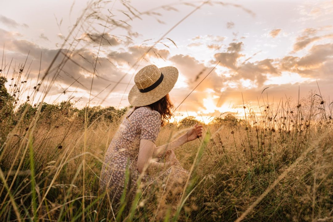 Girl with a hat during an August sunset