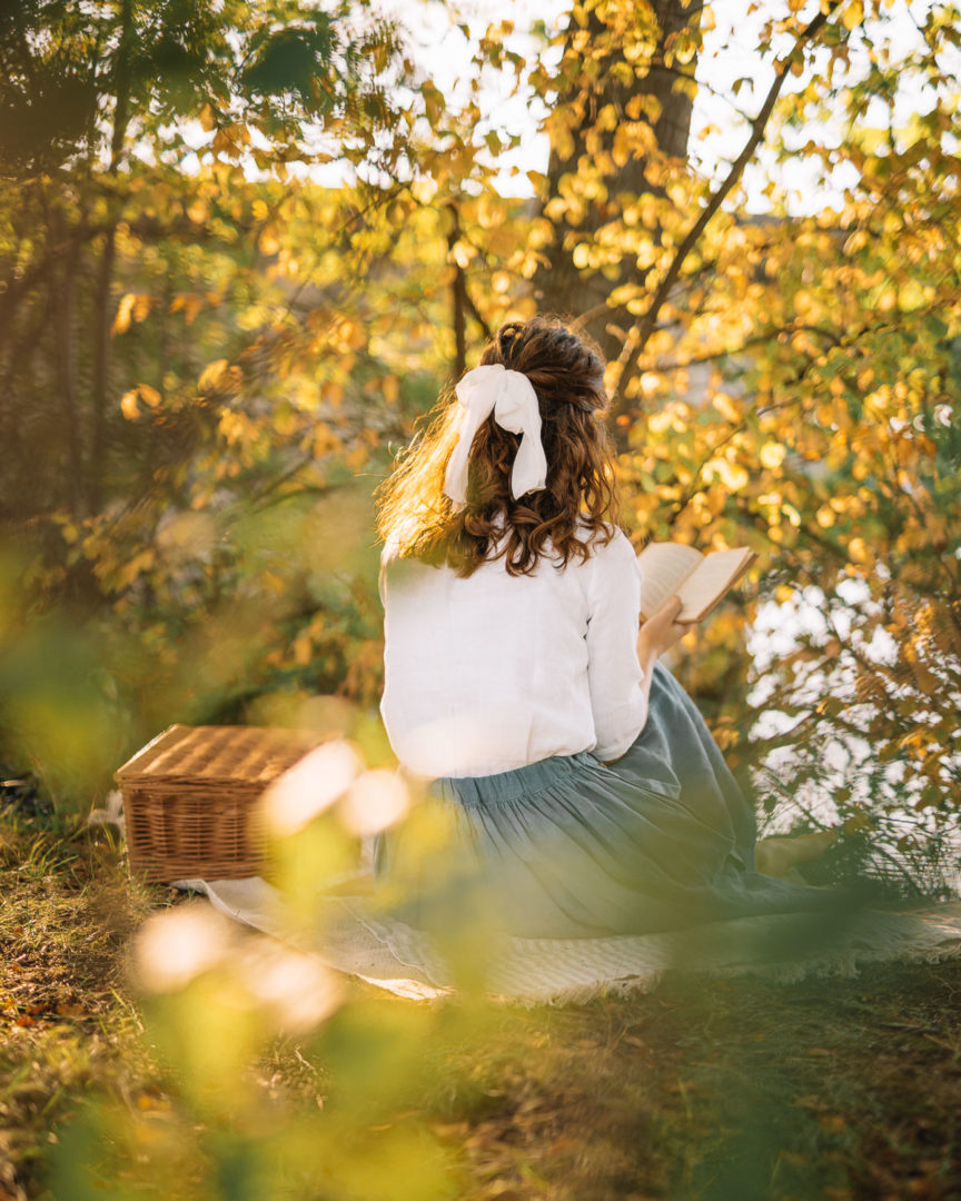Girl reading by the lake on a warm September afternoon
