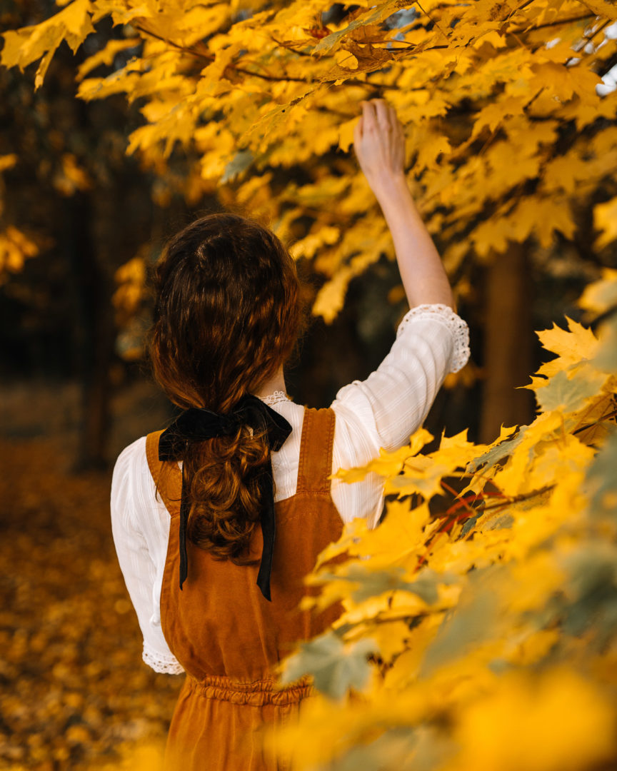 Girl reaching up for autumn leaves