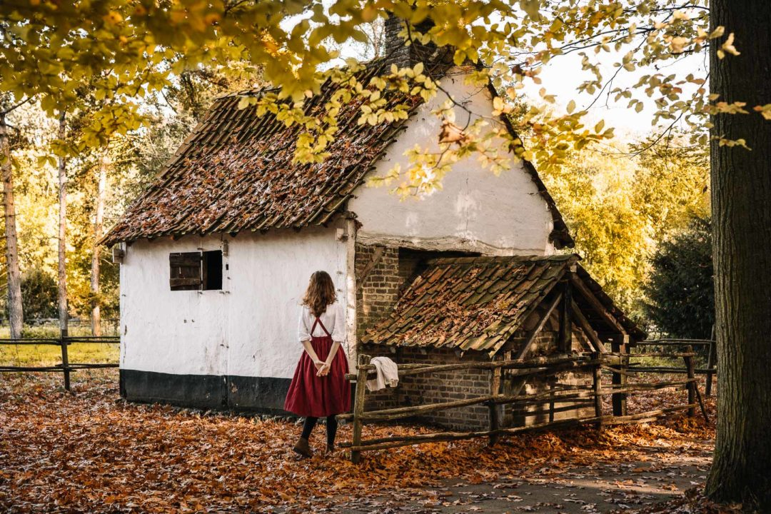 Girl in a dress next to an old farm during autumn