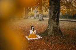 Girl sitting under an autumn tree reading a book
