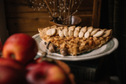 Slice of apple pie next to apples