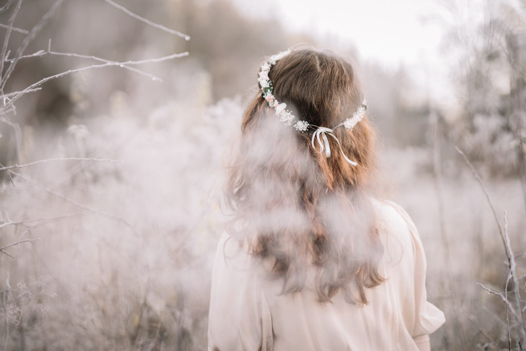 Girl wearing a floral crown in the midst of December frost