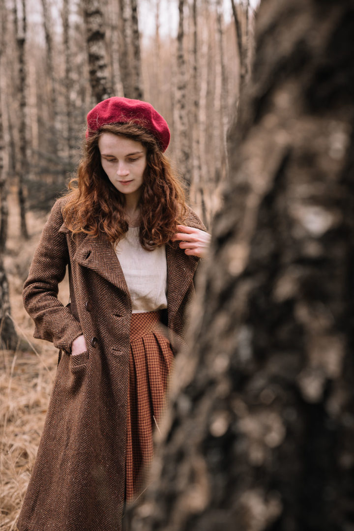 Girl wearing a 1930s coat walking in the forest during January