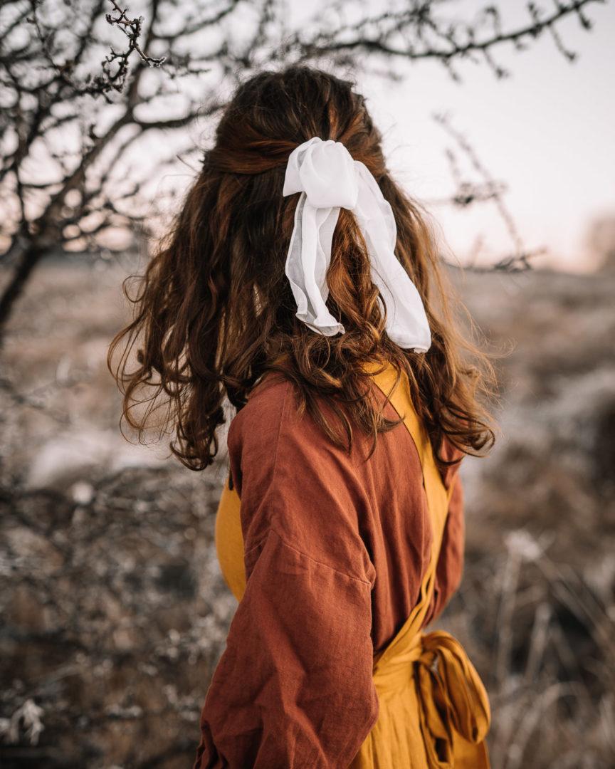 Girl wearing a pinafore dress in a frosty field