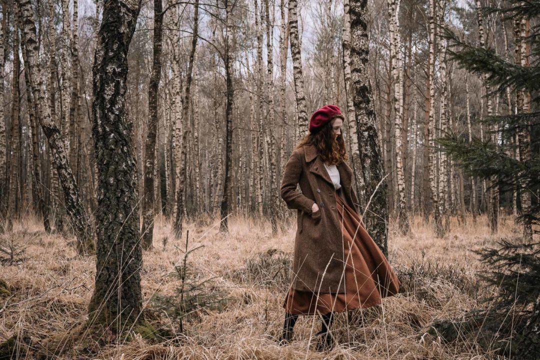 Girl wearing a 1930s coat in the forest during January