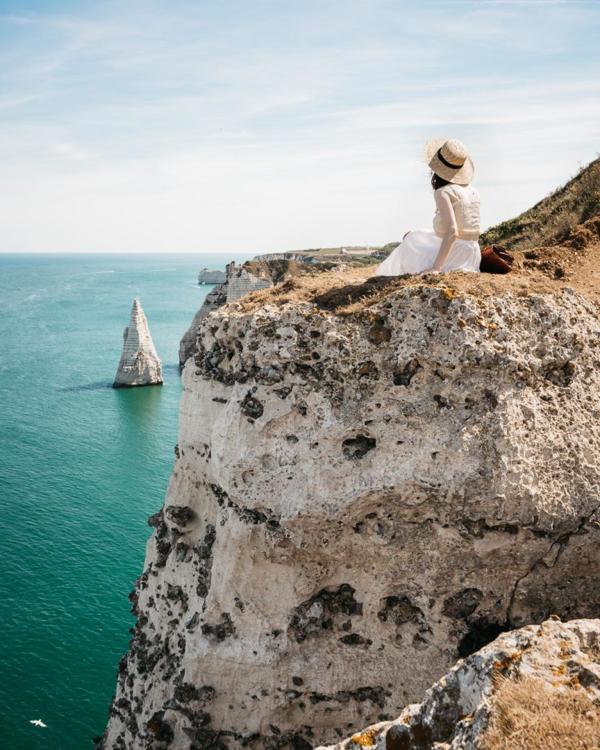 Girl sitting on top of the Étretat cliffs