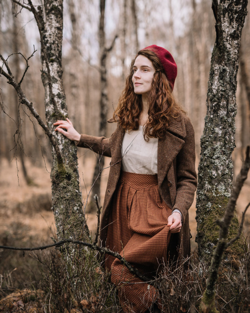 Girl wearing a 1930s coat and vintage skirt in the forest