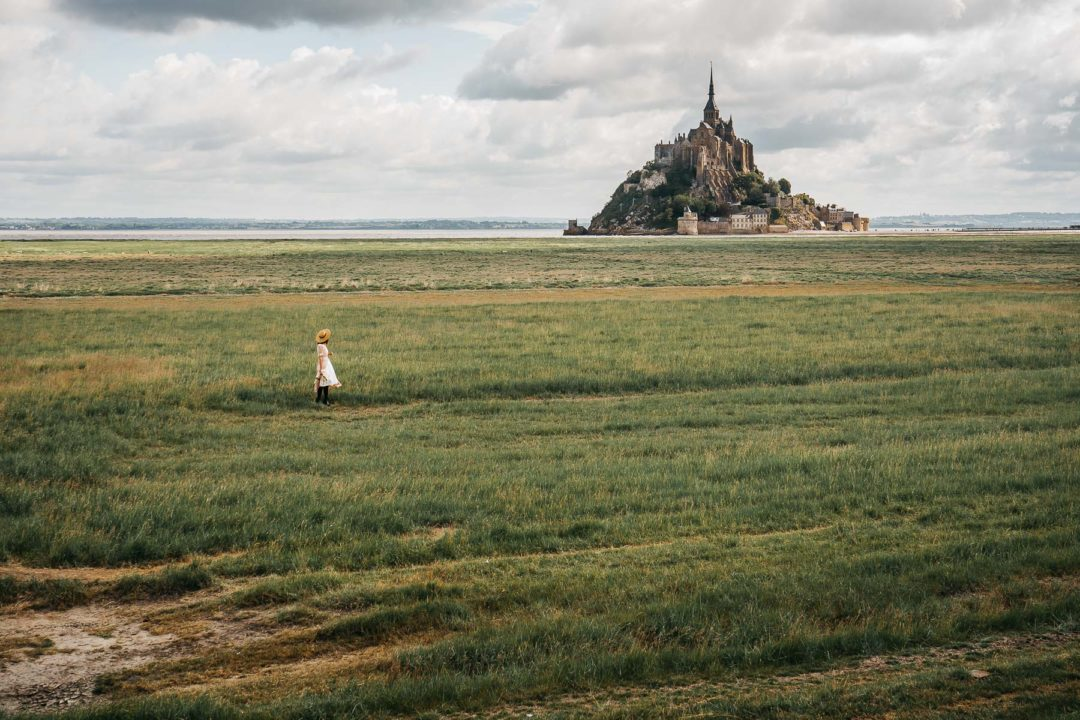 Mont Saint-Michel in the distance, girl in a dress in the foreground