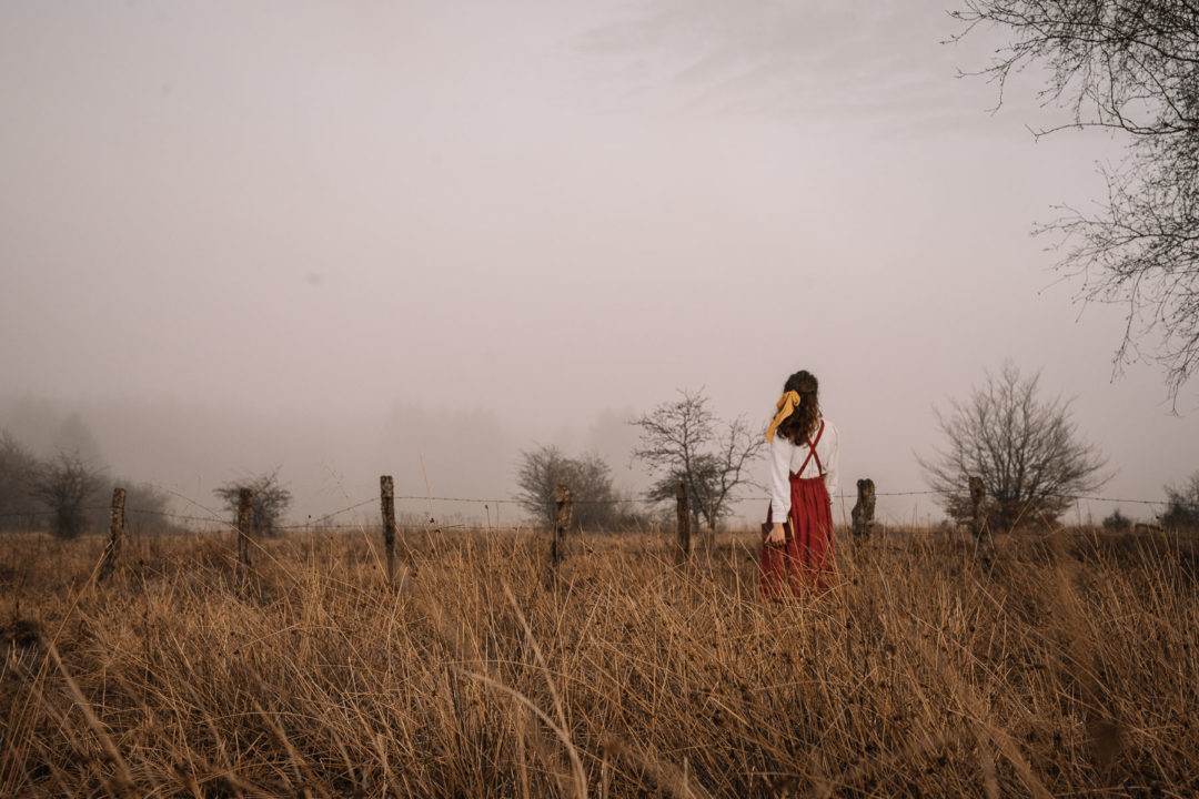Girl  in a pinafore dress standing in a foggy field