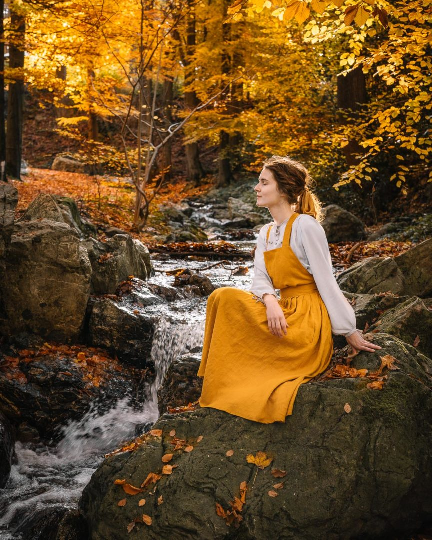 Girl in a pinafore dress sitting on a rock and enjoying the beauty of autumn