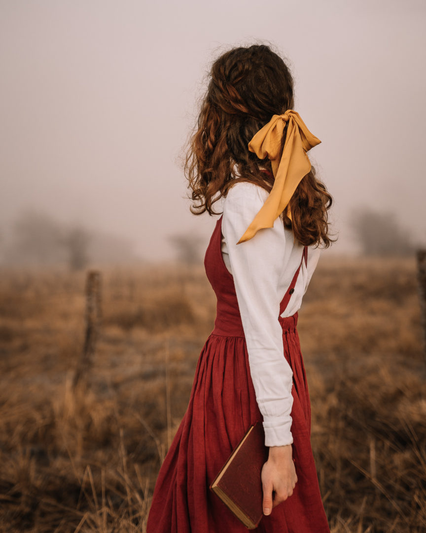 Girl in a pinafore dress holding a book in a foggy field