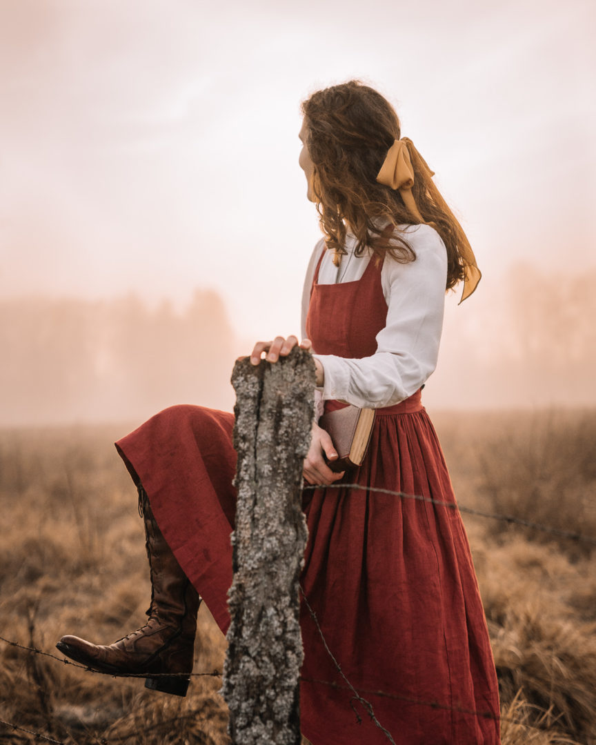 Girl wearing a pinafore dress trying to cross over the fence in a foggy field