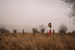 Girl standing in the middle of an empty and foggy field