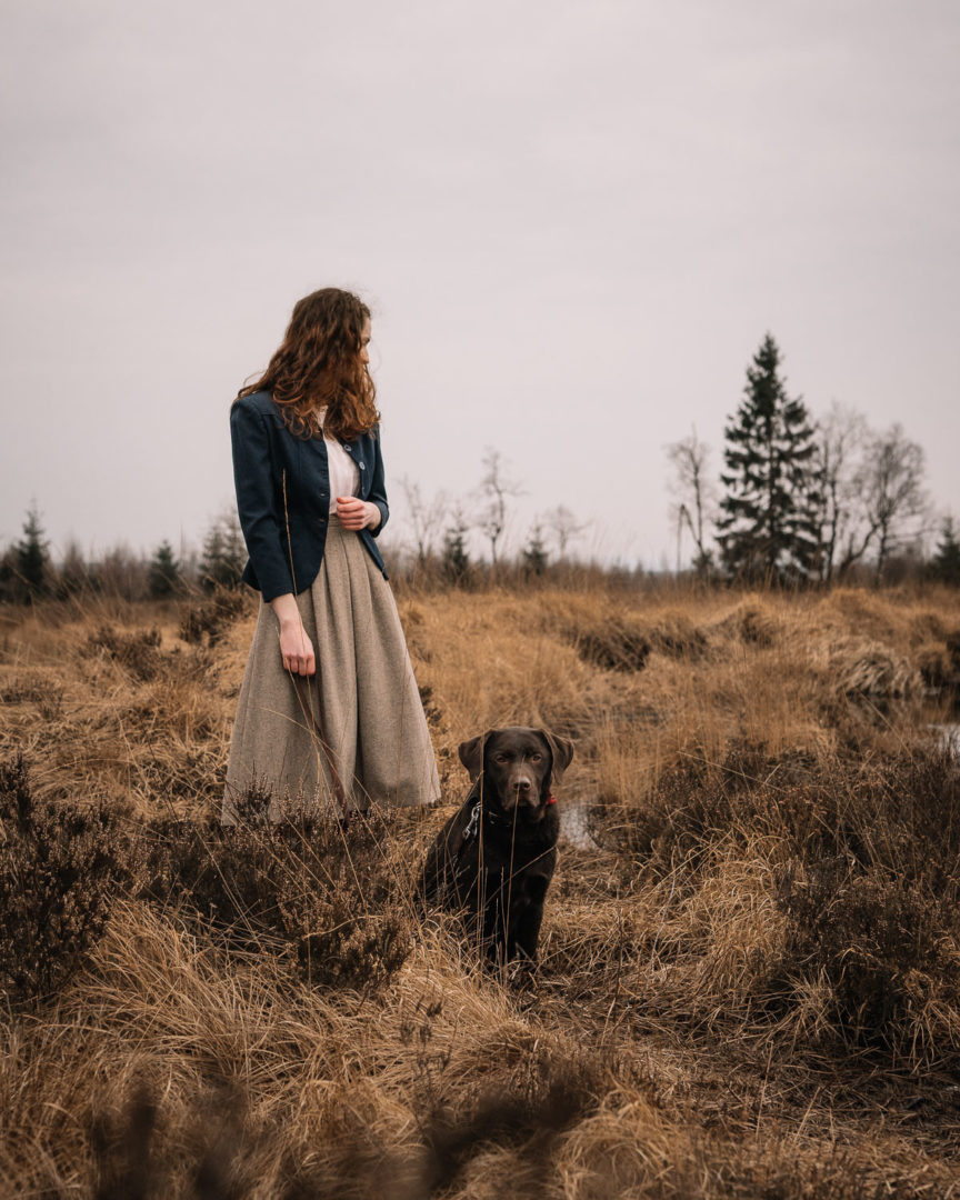 Girl and her dog taking a walk in nature during February