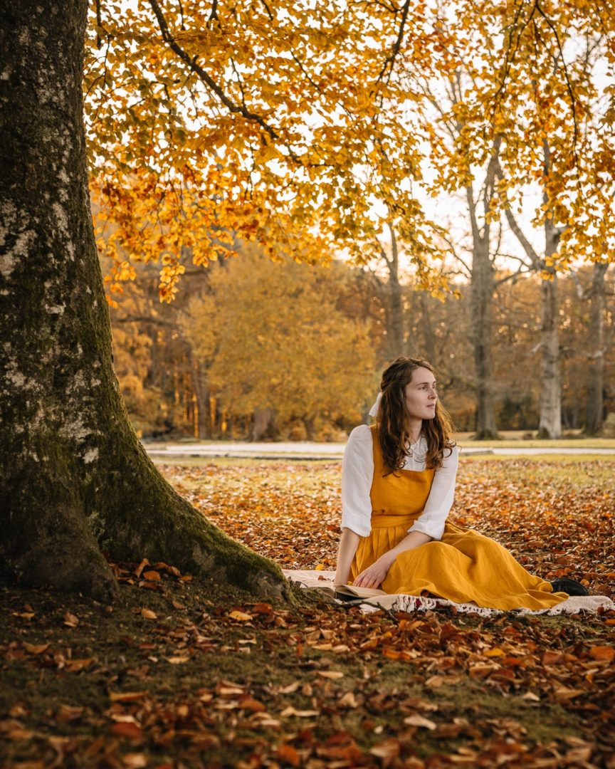 Girl wearing a linen pinafore dress by Isona Linen in the forest during autumn