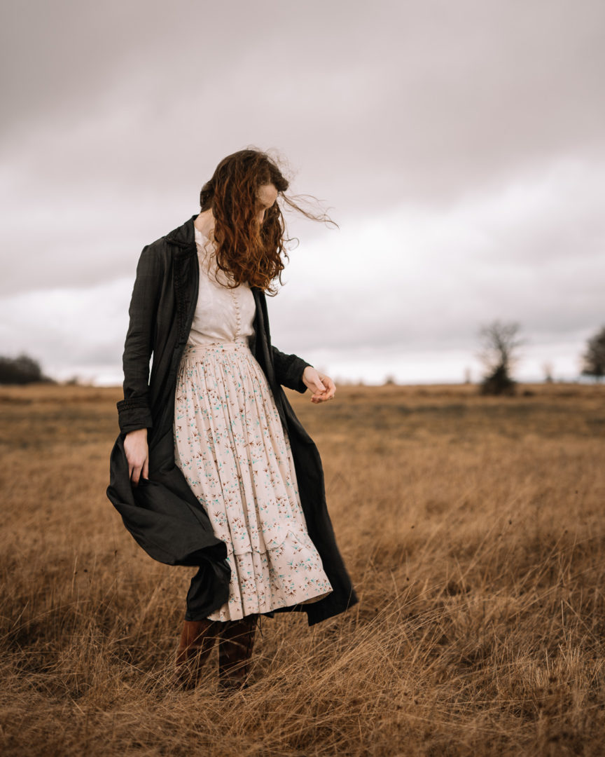 Girl wearing an Edwardian coat, enjoying a windy day during February