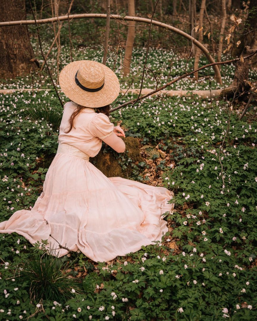 A girl in a 1930s dress sitting among the wood anemone.