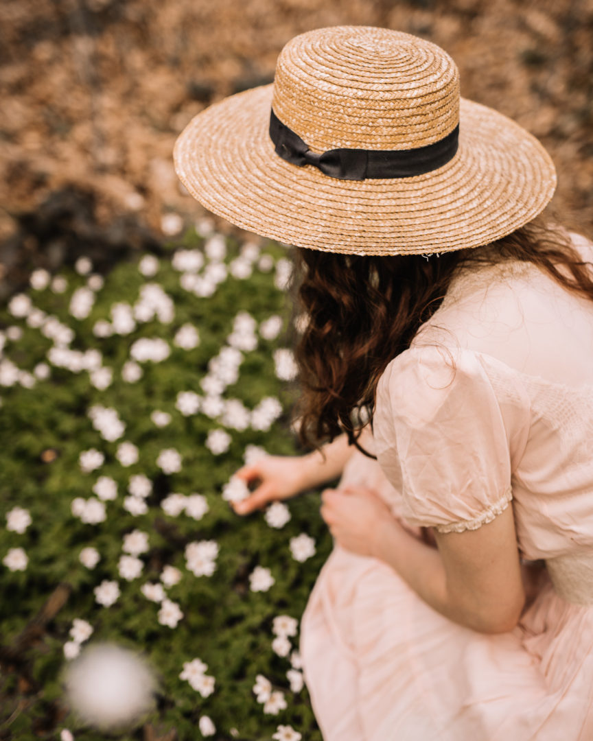 A girl in a 1930s dress among the wood anemone picking flowers.
