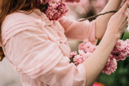 A girl in a pink dress entangled in pink cherry blossoms