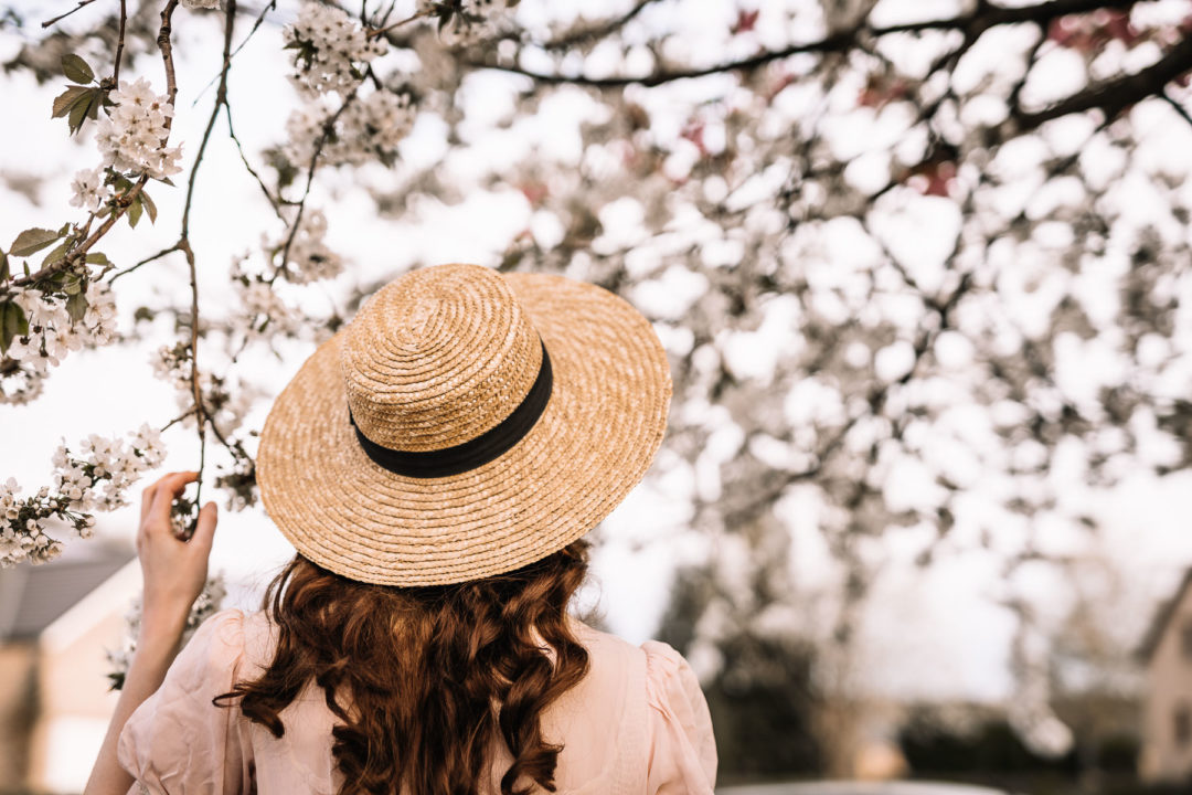 Girl in a straw hat under a cherry tree full of blossoms