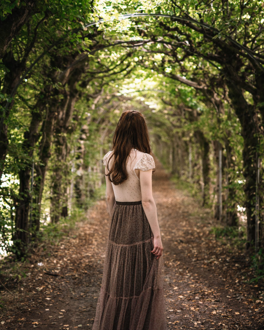 Girl wearing a madame shoushou dress under a tree tunnel