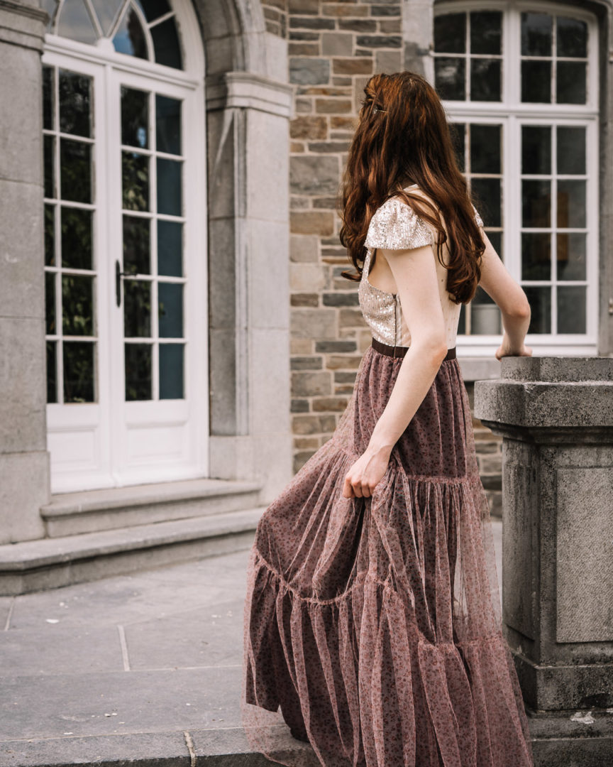 Girl wearing an elegant long dress climbing up the stairs