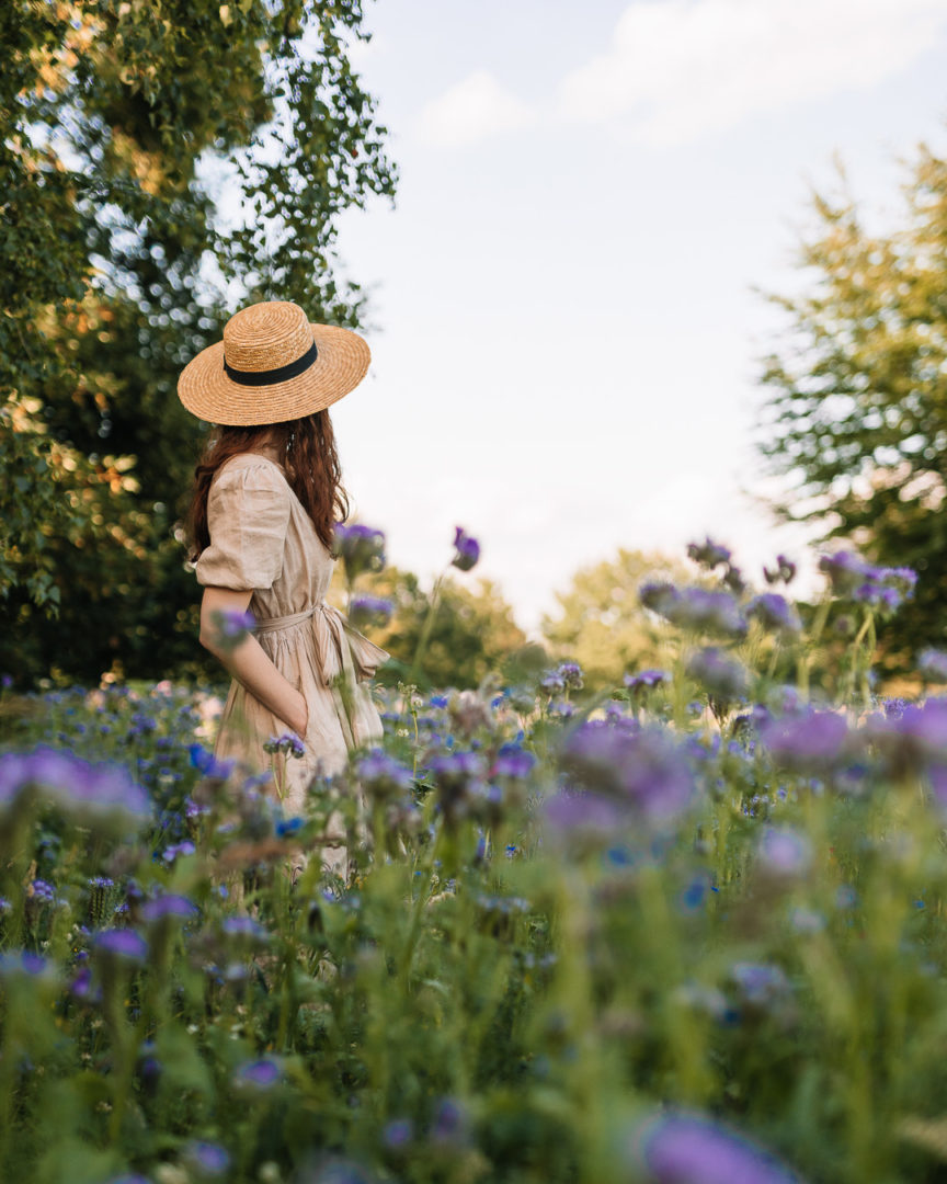 Girl with a straw hat wearing a TwoLINEN puff-sleeved dress in a field of blue wildflowers