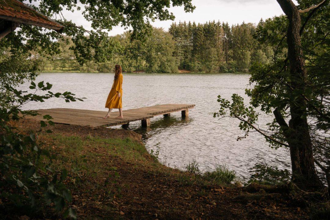 A girl wearing a TwoLINEN kimono robe next to a lake