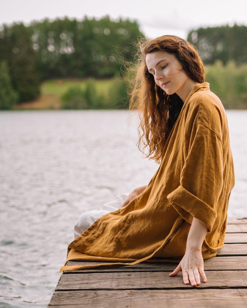 Close up shot of a girl wearing a TwoLINEN kimono robe next to a lake