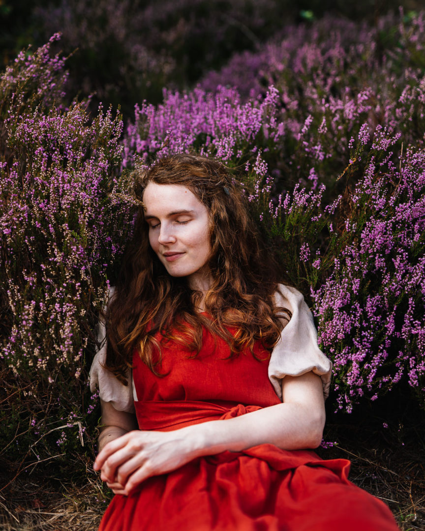 Woman in a pinafore dress lying down in the fields of heather.