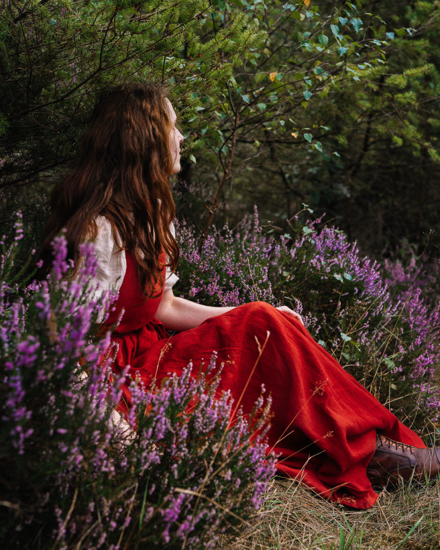 Woman in a dress sitting among fields of heather.