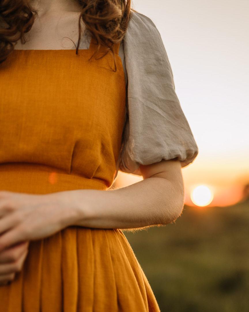 Close up shot of a girl wearing a TwoLINEN puff-sleeved linen dress against the golden sunset