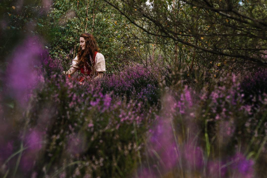 Woman hiding among fields of heather.