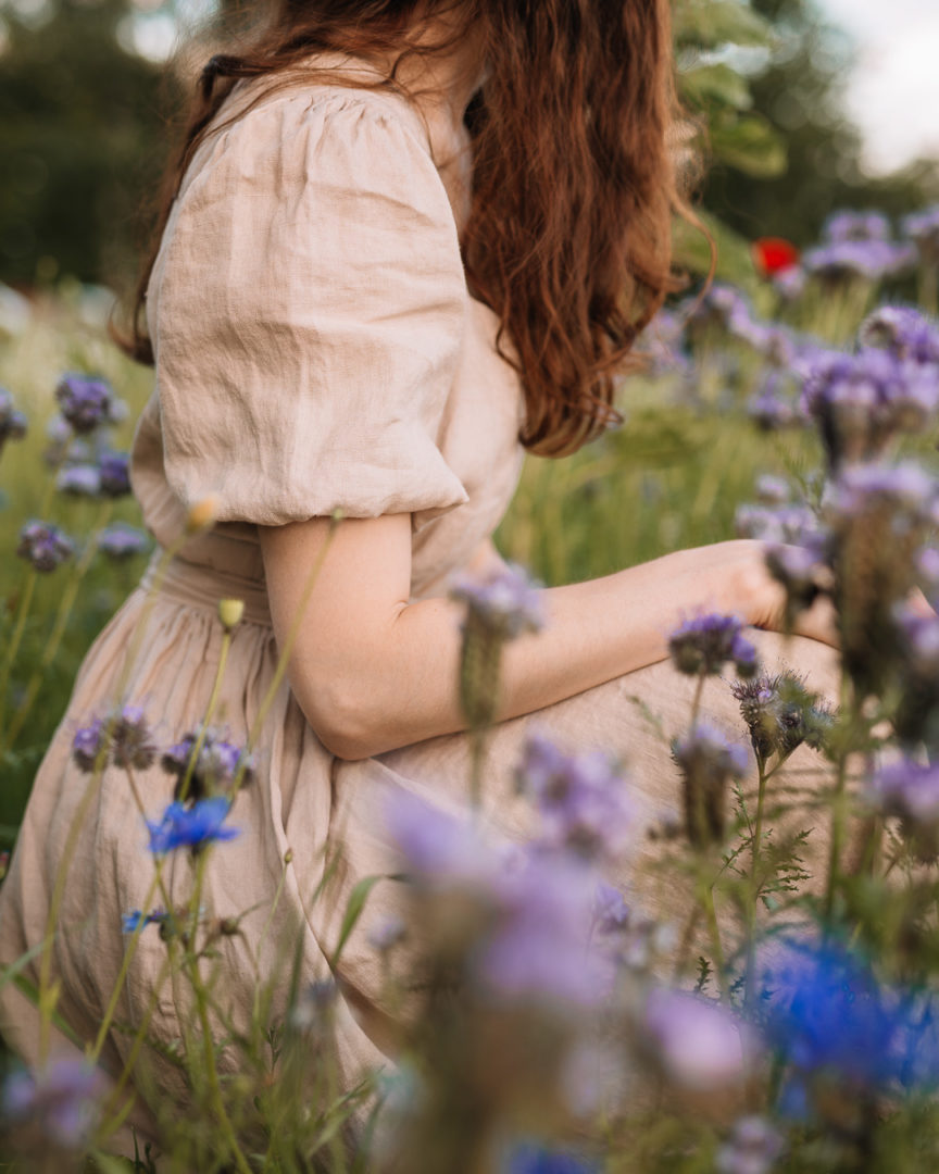 Close up shot of a girl wearing a TwoLINEN puff-sleeved linen dress in a field of blue wildflowers