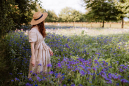 Girl with a hat standing in a field of blue wildflowers