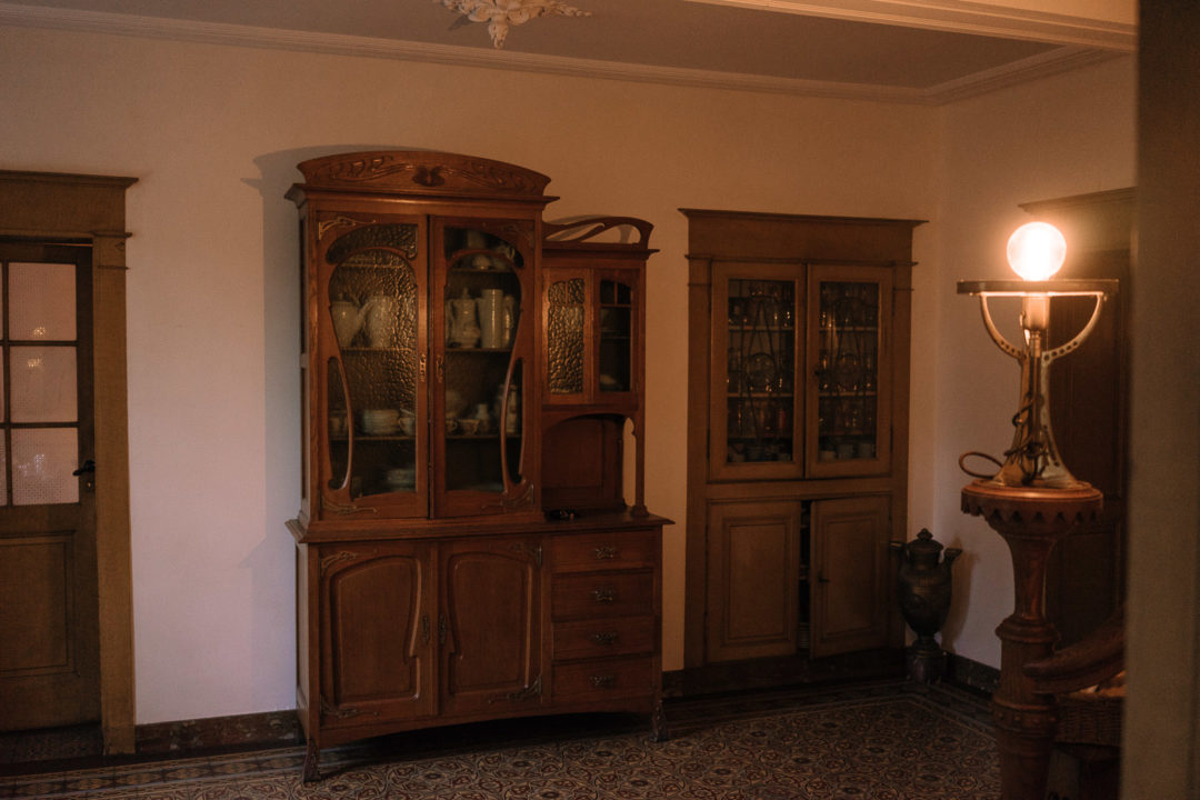 Art Nouveau china cabinet in the hallway of Aux Quatre Bonniers.