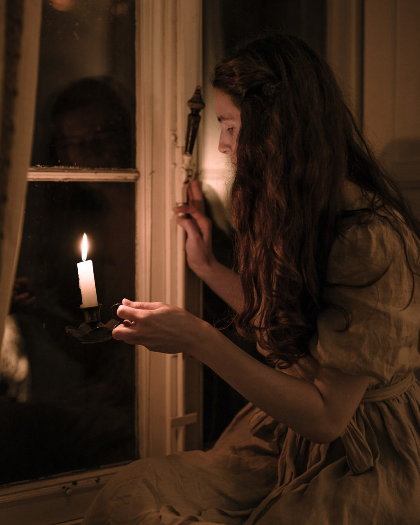Girl holding a candle next to a window at night.