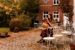 Woman reading a book on the terrace of Aux Quatre Bonniers