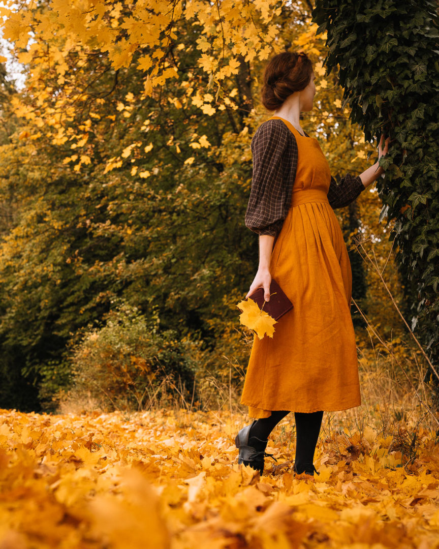 Stories of autumn, a woman in a pinafore dress surrounded by golden leaves during autumn.