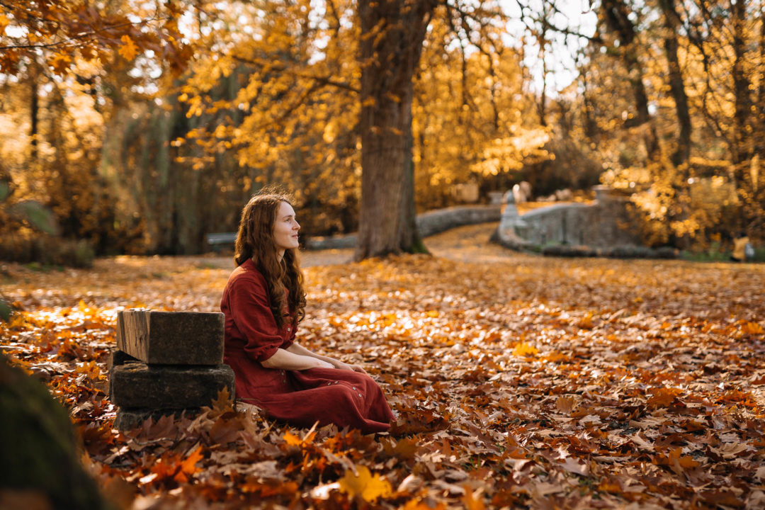 Stories of autumn, a woman in a dress sitting among golden leaves during autumn.