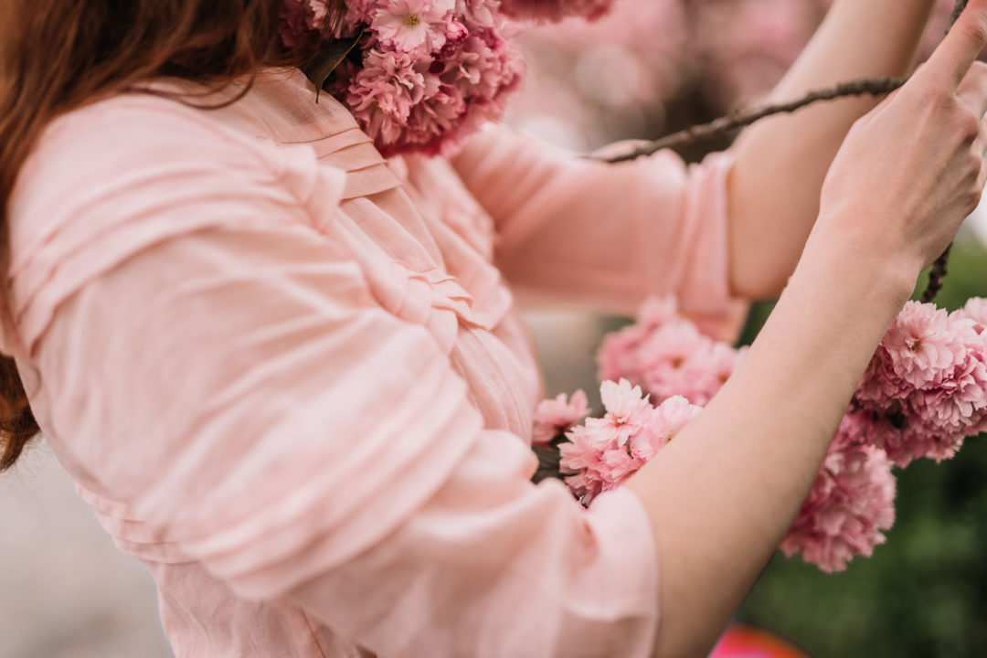 Woman holding cherry blossoms during the spring of 2020