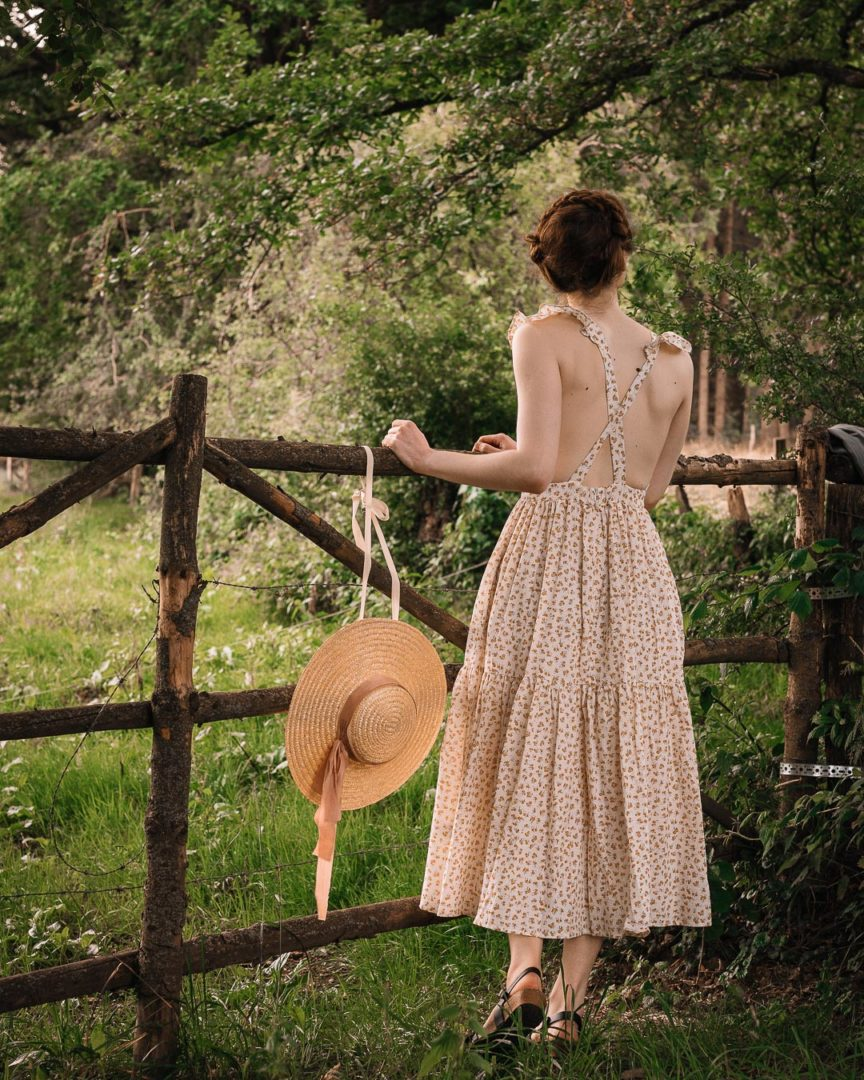 Woman in a dress in front a wooden fence during a summer day in 2020