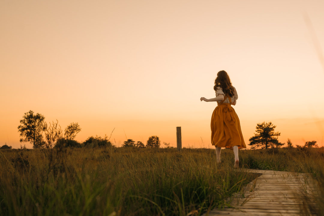 Woman in a dress running towards the golden sunset