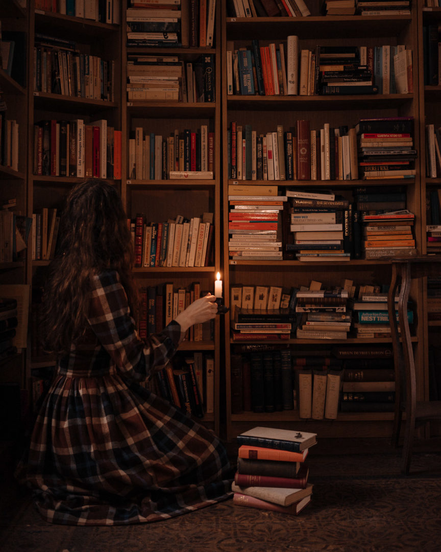 Woman holding a candle in front of a bookshelf, looking at all the books read during 2020